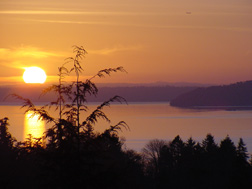 Sun setting behind Point Defiance and Gig Harbor, WA.